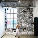 Artist Lauren Asta standing in front of her Threadless Mural