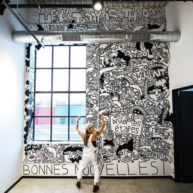 Artist Lauren Asta standing in front of her Threadless Mural