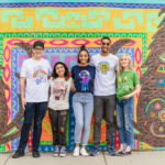 Guys and girls wearing t-shirts in front of mural