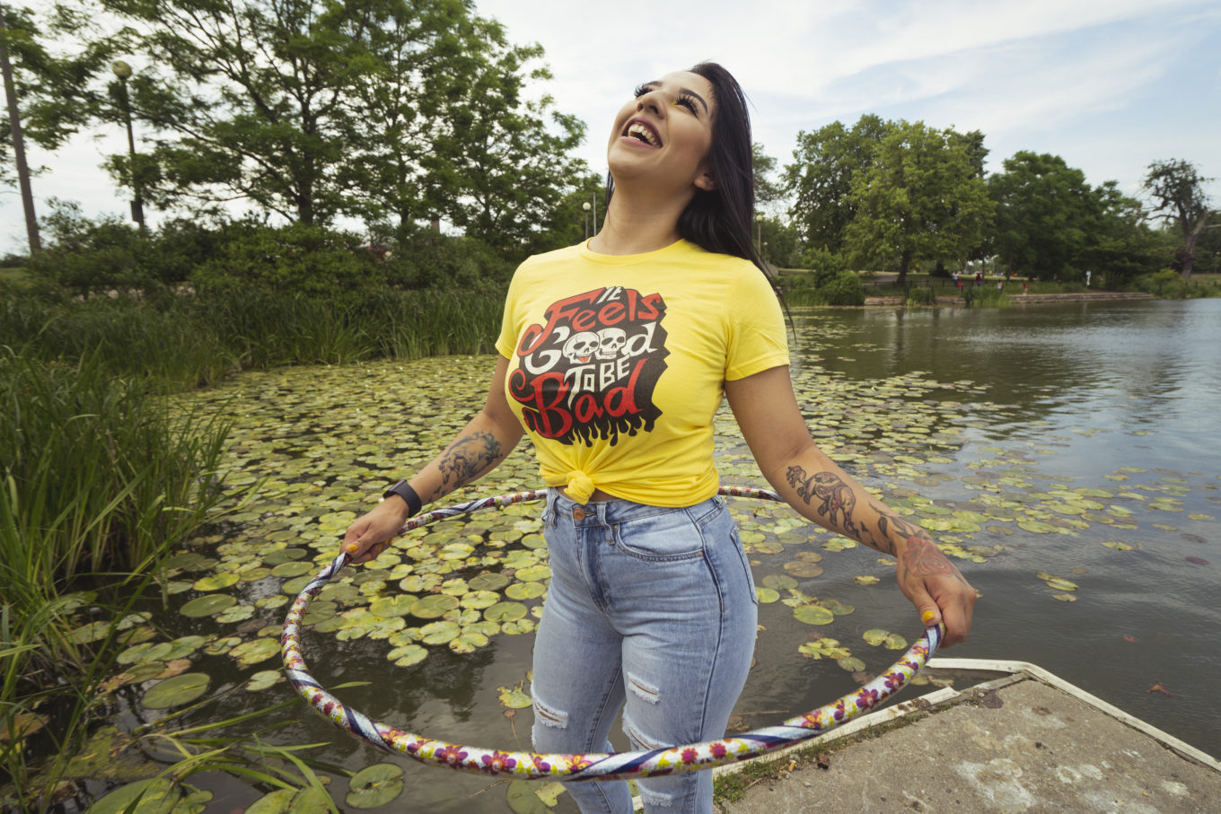 Woman wearing a t-shirt, next to a lake, smiling and hula hooping